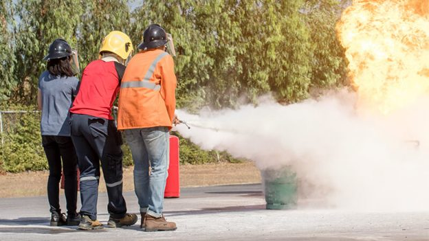 three people training for fire similation with fire extinguisher